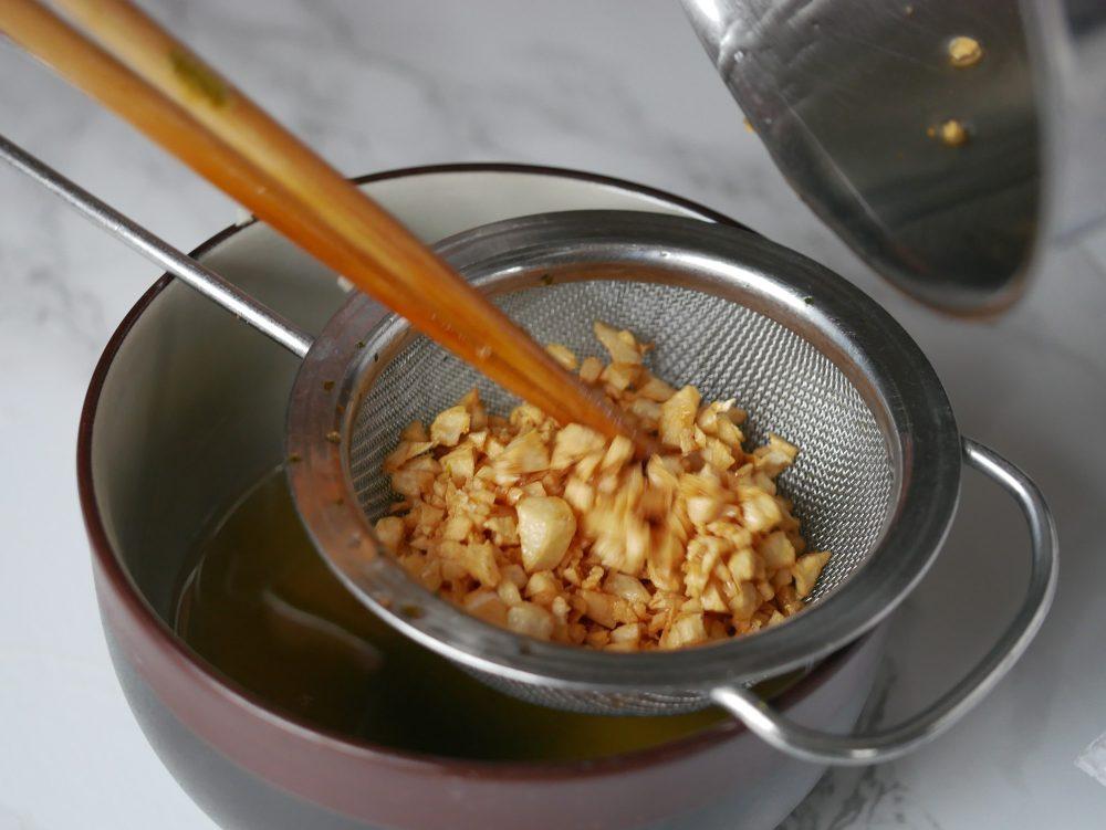 Zeef de knoflook, die nog niet goudbruin is, uit de hete olie.