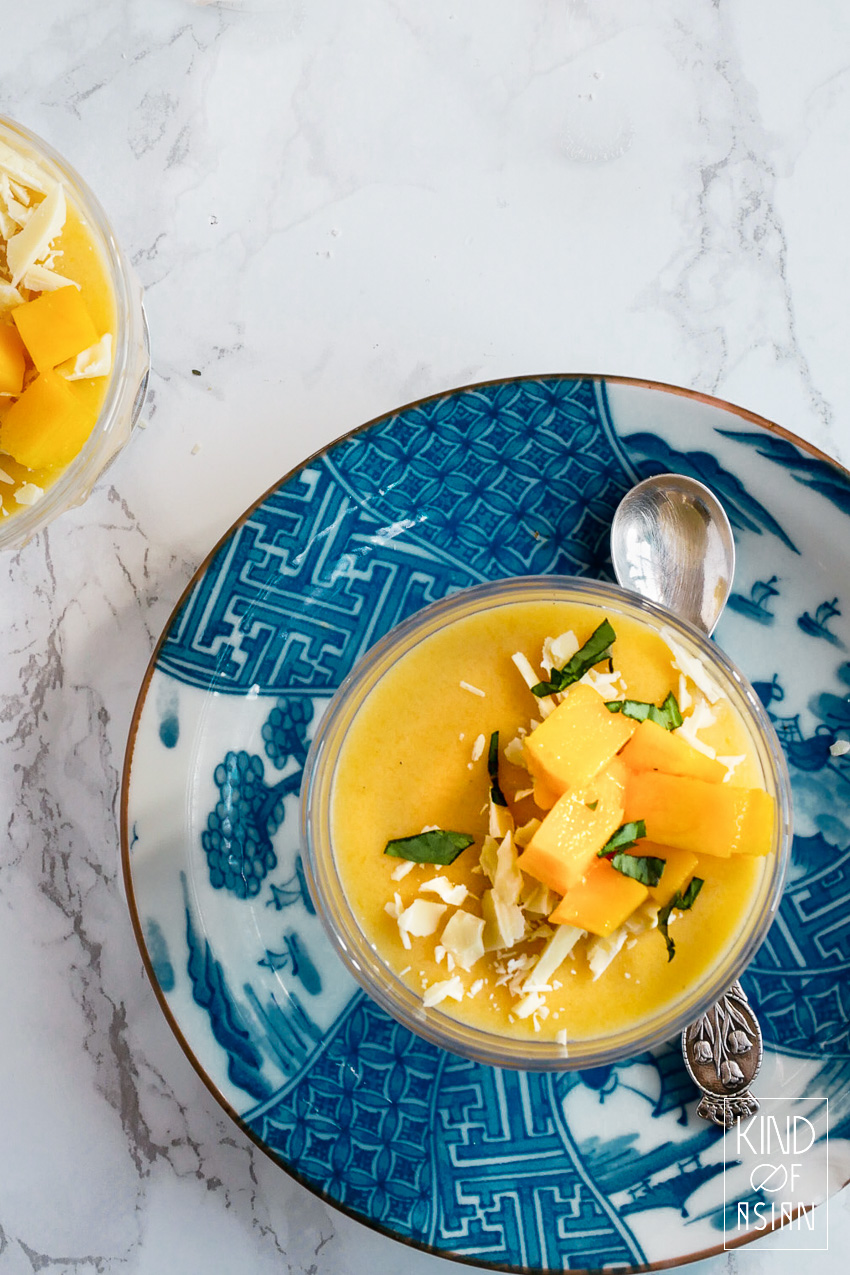 vegan mangopudding in glas op blauw bord
