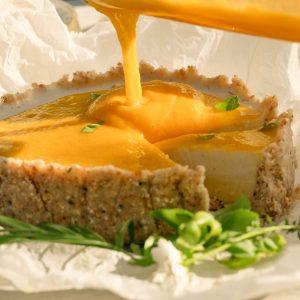 Deze zomerse, vegan Thaise mango taart heeft een bodem van kokos, limoenblad, amandel en geroosterd rijstpoeder. De vulling bestaat uit drie lagen: een romige ganache van witte chocolade en limoenrasp, een frisse, lichte panna cotta van kokosmelk en citroengras en als laatste een zoete coulis van mango. Voor deze taart hoef je de oven niet eens aan te zetten.