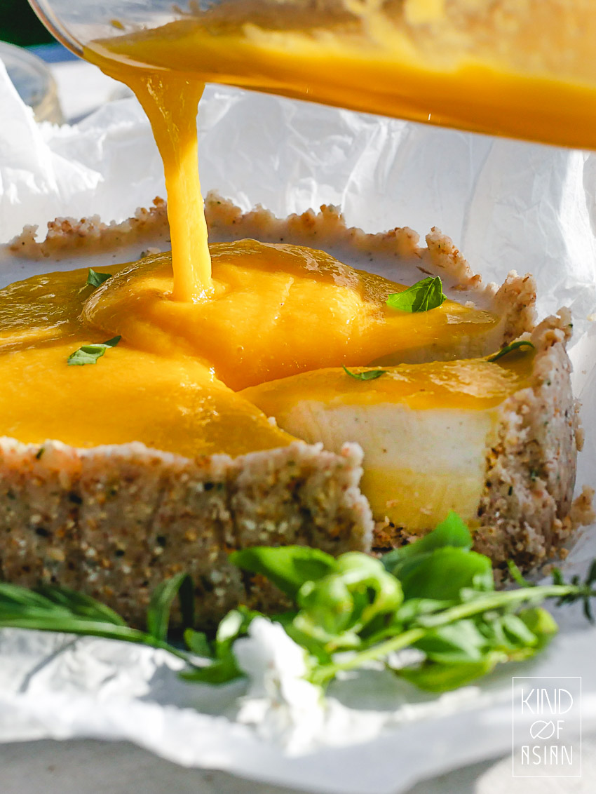 Deze zomerse, vegan Thaise mango taart heeft een bodem van kokos, limoenblad, amandel en geroosterd rijstpoeder. De vulling bestaat uit drie lagen: een romige ganache van witte chocolade en limoenrasp, een frisse, lichte panna cotta van kokosmelk en citroengras en als laatste een zoete coulis van mango.
