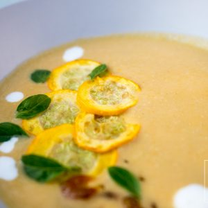 Vegan yellow zucchini coconut soup with fragrant Thai herbs garnished with Thai basil, grilled yellow zucchini and coconut cream