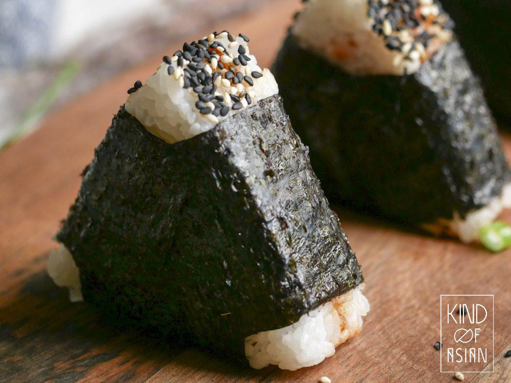 Je wil geen mega compacte onigiri rijstballetjes maar ook niet dat ze uit elkaar vallen? Vouw er 3 korte strookjes om elke rand.