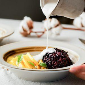 Gestoomde Thaise zwarte kleefrijst met mango en warme kokossaus.