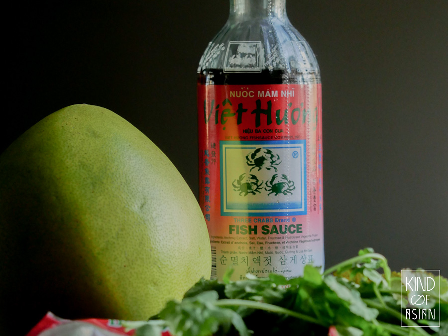 Big pomelo with green yellow skin and a bottle of fish sauce