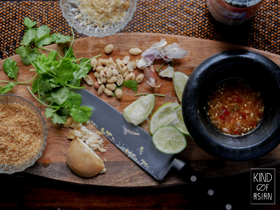Making Thai dressing with mortar and pestle. Ingredients for the dressing: yellow palm sugar, lime, garlic and chili.