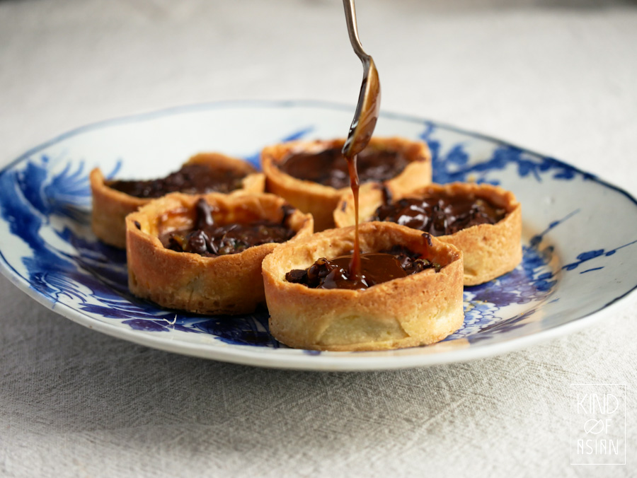 Mini vegan chocolade ganache taartjes met koekbodem worden gevuld met karamelsaus.