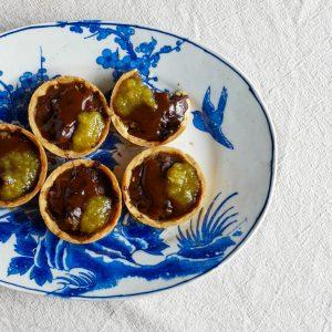 Mini vegan chocolade ganache taartjes met krokante bodem, warme en kleverige karamel van donkere palmsuiker en warme gemberjam.