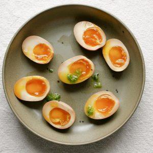Gehalveerde eieren met zachte dooiers op een groen bord.