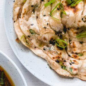 Voor dit brood met dunne laagjes hoef je de oven niet aan te zetten. Je bakt in een koekenpan de Chinese flatbread met lente-ui en 5-spice aan beide kanten krokant en het midden blijft het zacht en chewy.