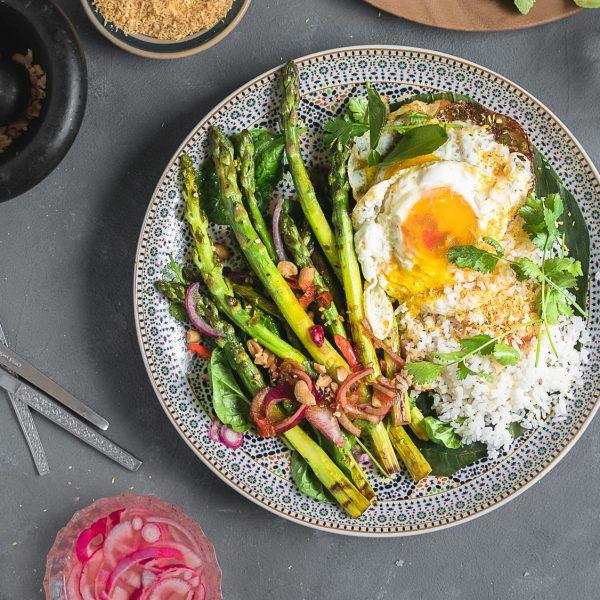 Verse kruiden, knapperige pinda's, veel groenten, in friszure en pittige dressing met fluffy kokosrijst. Deze vegetarische salade van groene asperges in Thaise dressing ga ik deze zomer heel vaak maken!