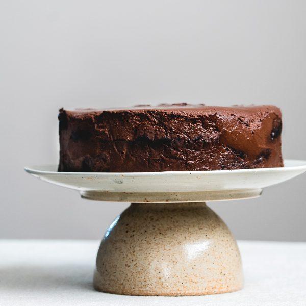 Luchtige chocoladecake met zachte truffelcrème van pure chocolade op een beige plateau