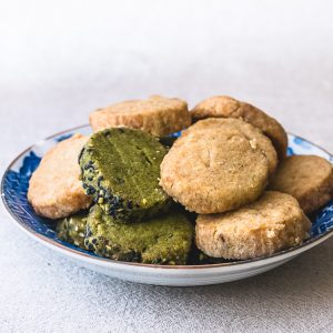 Voor dit basisrecept voor vegan koekjes hoef je slechts 4 ingrediënten- die je waarschijnlijk al in huis hebt- te mengen in 1 kom. Ze zijn lekker bros, licht gezoet en smaken naar boterkoekjes. Groene en gele koekjes op een schoteltje.