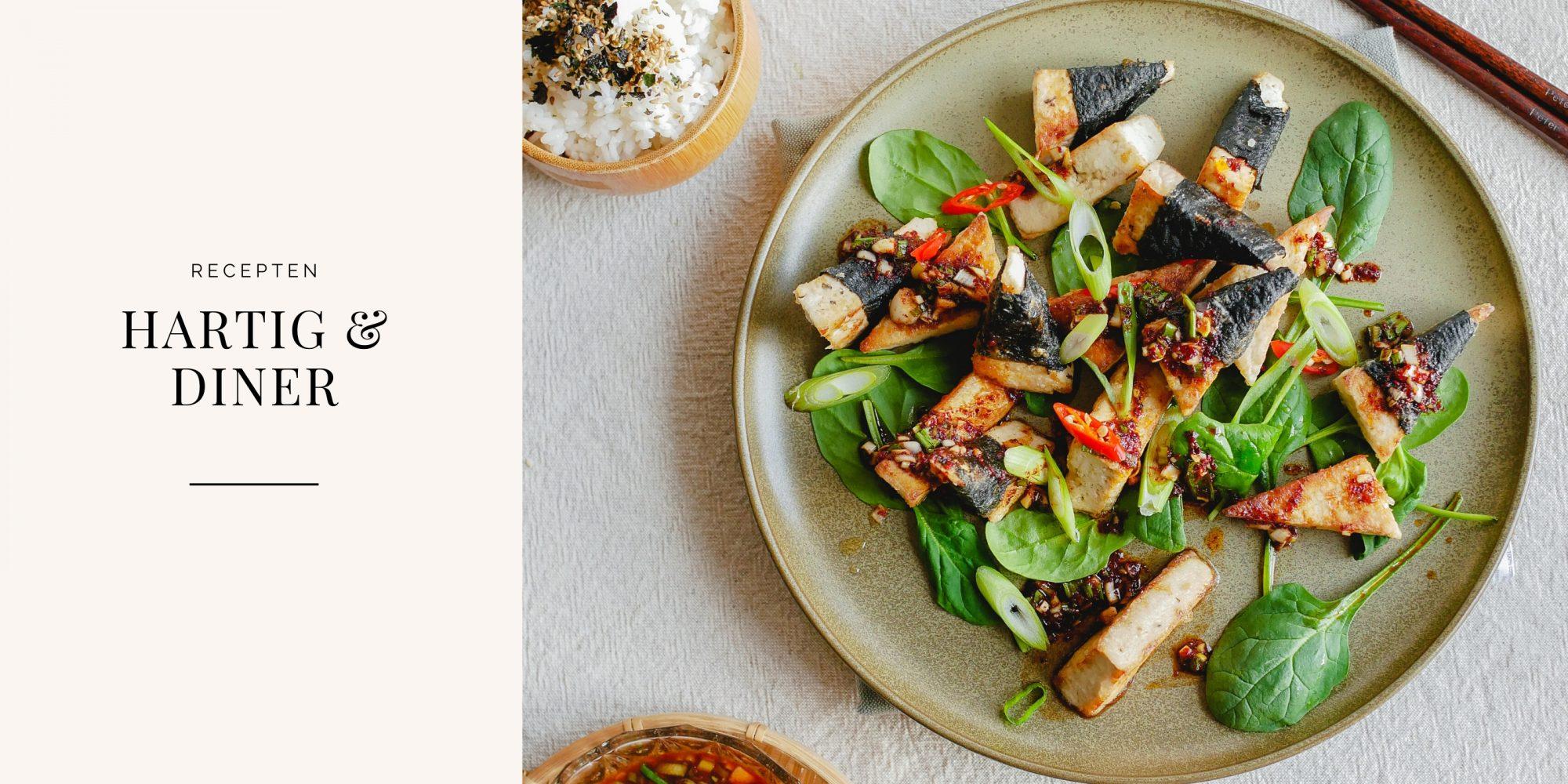 Plakjes tofu met nori in pittige saus op een rond bord.