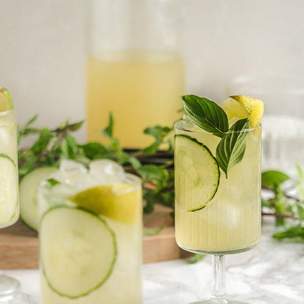 Limonade is een snelle dorstlesser maar een alcoholvrije mocktail met komkommer en Thaise basilicum is zo intens fris en kruidig dat je nipjes wil nemen. Zonnig tafereel met twee glaasjes met mocktail en komkommer.