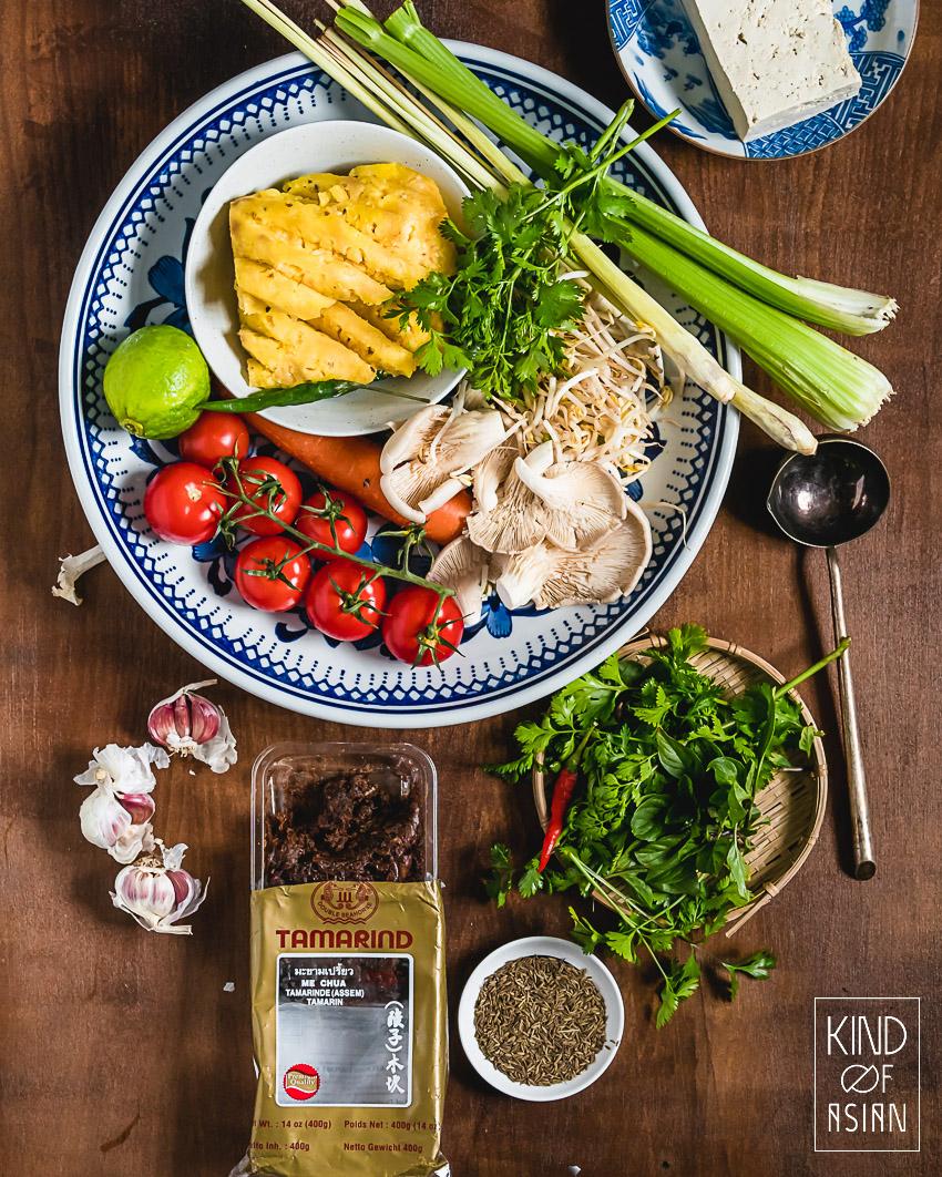 Op de grote ronde schaal liggen verse ananas, tomaat, citroengras - verder tamarinde, komijn, koriander en andere verse kruiden voor de vegan Vietnamese tamarinde soep.