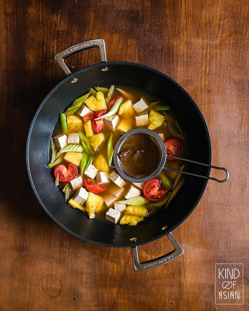 De tamarinde wordt door een zeefje gedrukt in de hete soep met ananas, tomaat en selderij.