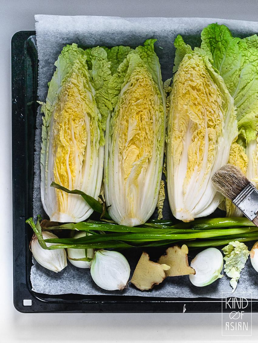 Chinese kool, witte uien, gember en lenteui op een bakplaat.