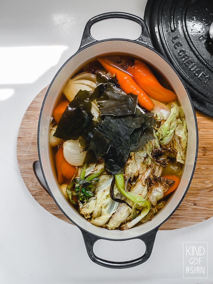 Zware pan met wortel, uien, groenten en kombu zeewier: vegan Aziatische groentebouillon.