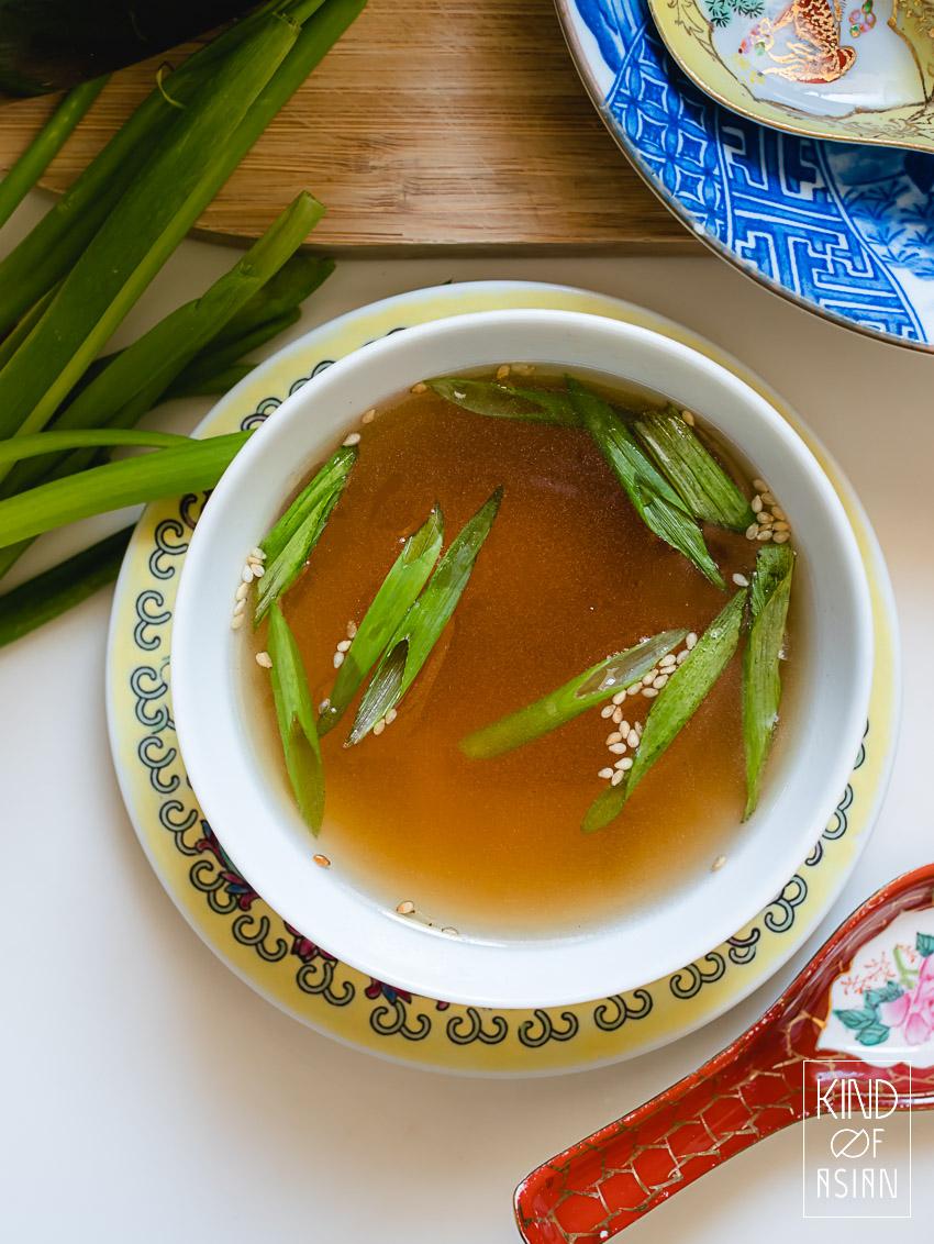 Chinese kom met heldere, goudgele vegan Aziatische groentebouillon met lenteui en sesam.