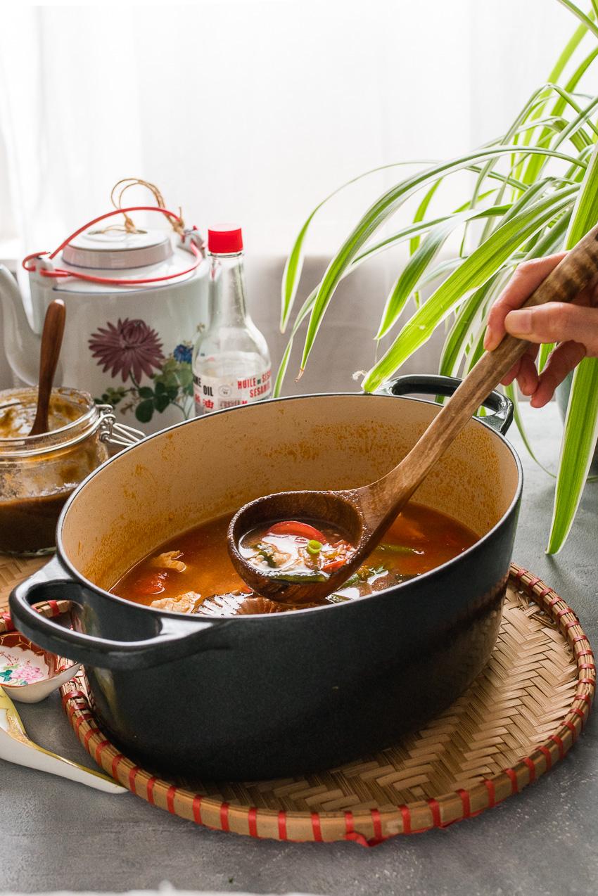 Pan met vegan Chinese tomatensoep en soeplepel