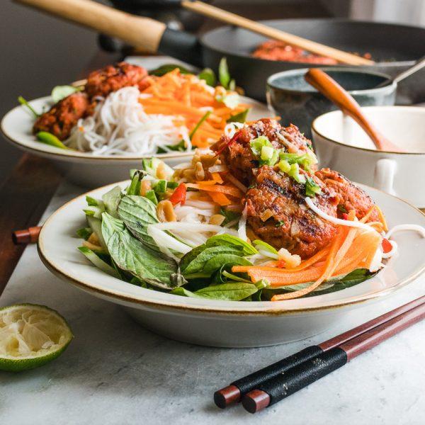 Twee borden Vietnamese rijstnoedels en vega burgers