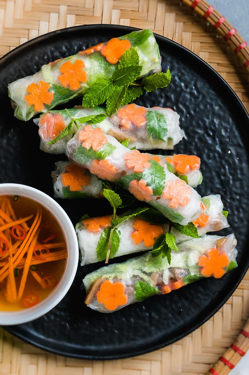 Bord met vegan Vietnamese summerrolls met sticky gebakken koningszwammen
