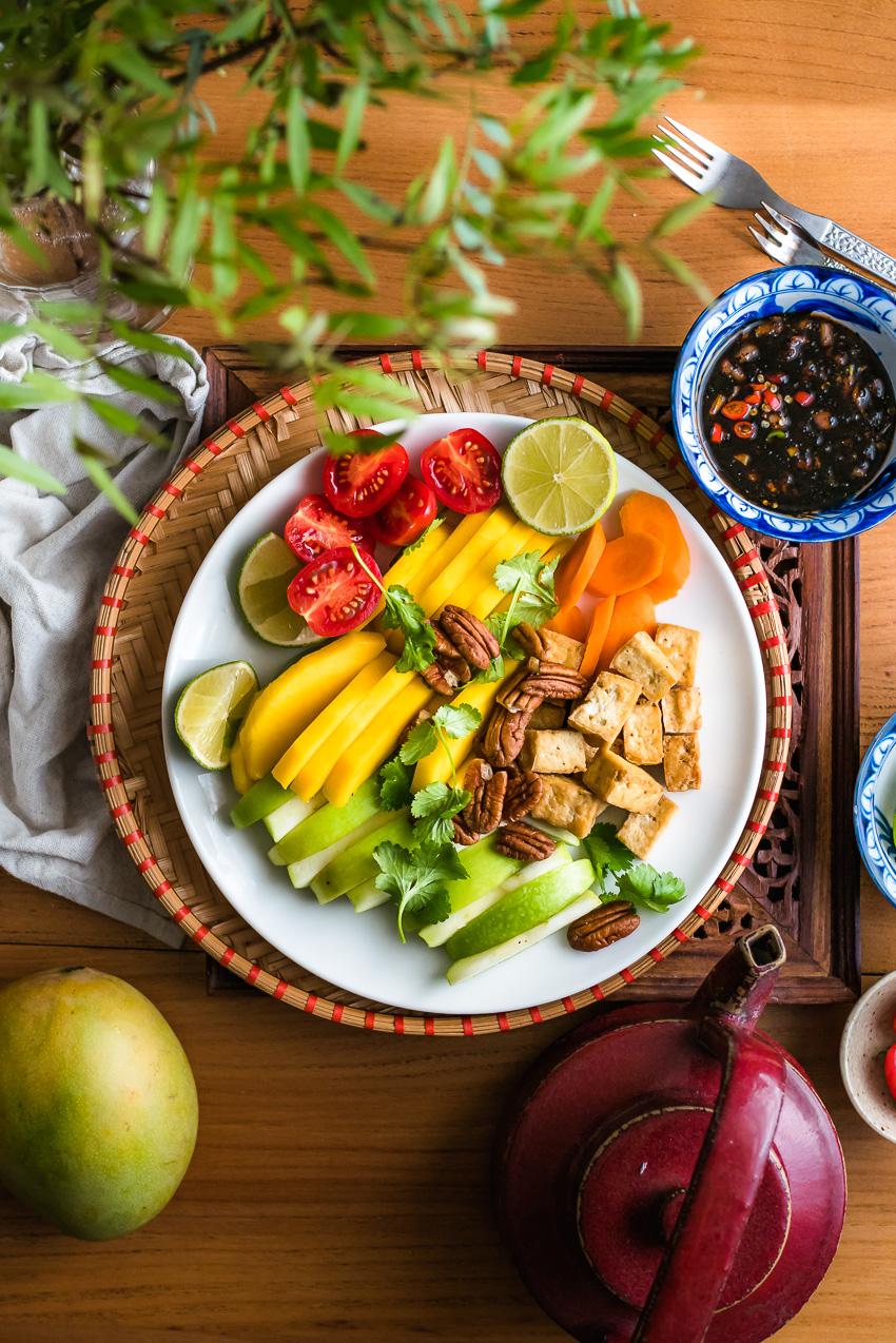 Fruit op wit bord met Thaise vegan 'vissaus' met palmsuiker